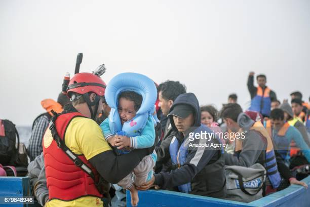 A member of the Spanish NGO Pro Activa helps a baby to getting board during a rescue in the Mediterranean Sea Italy on May 06 2017