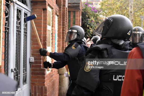 A member of the spanish police is seen destroying a door with a hammer National Police entered by force in the High School of L´Hospitalet City where...