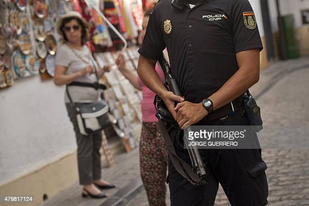 A member of the Spanish special police unit patrols near the Mezquita the MosqueCathedral of Cordoba on July 7 2015 Spain is facing its highest level...