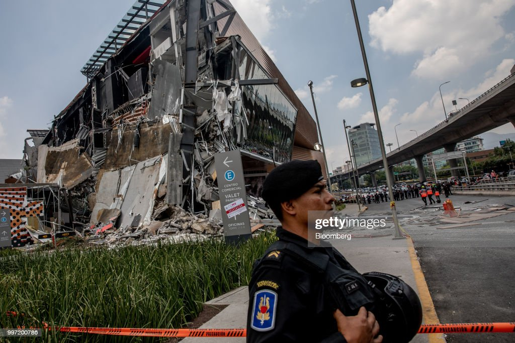 A member of the special forces stands in front of the collapsed section of the Artz Pedregal shopping mall in Mexico City, Mexico, on Thursday, July 12, 2018. A section of the high-end fashionmallinaugurated a mere three months ago collapsed Thursday afternoon in Mexico City. Photographer: Alejandro Cegarra/Bloomberg via Getty Images