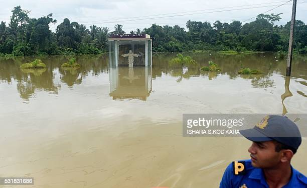 A member of the Sri Lankan Navy travels by boat past a submerged statue of Jesus Christ through the floodwaters in Pugoda about 35 kms from capital...