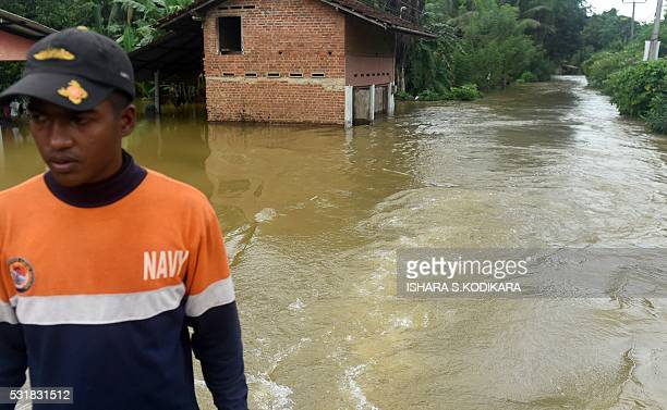 A member of the Sri Lankan Navy travels by boat through the floodwaters in Pugoda about 35 kms from capital Colombo on May 17 2016 Heavy rains...