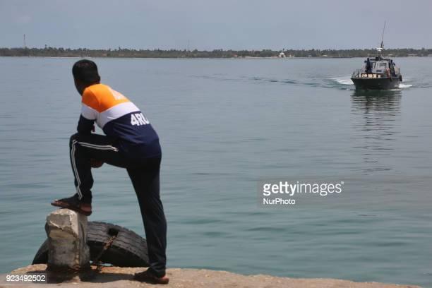 Member of the Sri Lankan Navy waits for a naval boat to arrive at Kurikadduvan Harbour in Northern Sri Lanka