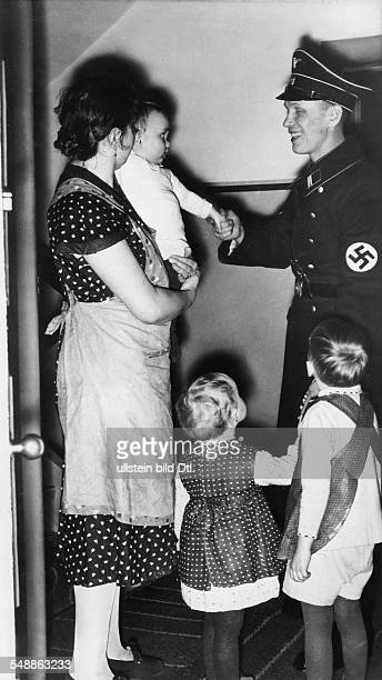 Member of the SS saying goodbye to his family before going to work on sunday morning Photographer Heinz Fremke Published by 'Die Braune Post' 18/1939...