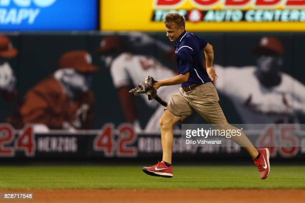 A member of the St Louis Cardinals grounds crew removes a kitten from the field in the sixth inning during a game against the Kansas City Royals at...