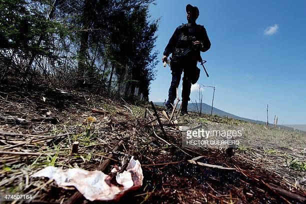 A member of the state police stands on May 23 2015 by a bloodstain during a search for evidence inside the ranch along the JaliscoMichoacan highway...