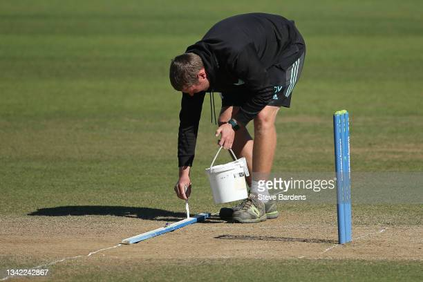 Member of the Surrey ground staff repaints the crease line on the wicket on day four during the LV= Insurance County Championship match between...