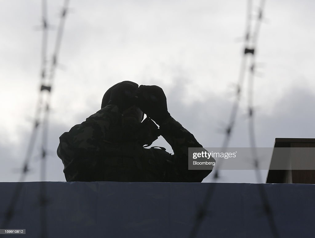 A member of the Swiss army looks out from a security tower near to the Congress Center, the venue for the World Economic Forum (WEF) in Davos, Switzerland, on Tuesday, Jan. 22, 2013. As policy makers and executives debate the latest remedies to draw a line under Europe's worst crisis since World War II, Swiss officers are now using the World Economic Forum as a testing ground for plans to turn the entire country into a fortress. Photographer: Simon Dawson/Bloomberg via Getty Images