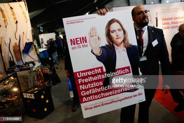 A member of the Swiss gunrights advocacy group ProTell holds a placard reading No to May 19 injustice hostile to freedom useless dangerous and...
