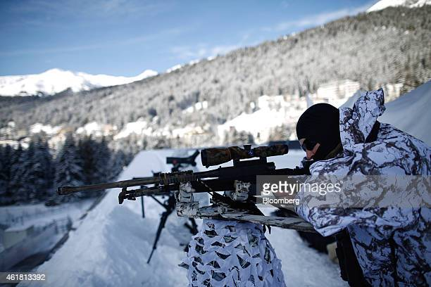 A member of the Swiss Police looks through his rifle sight during surveillance operations from a rooftop ahead of the World Economic Forum in Davos...