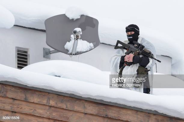 A member of the Swiss special police force takes position on a rooftop at the opening of the World Economic Forum annual meeting in Davos on January...