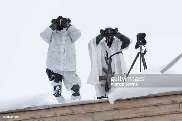 Member of the Swiss special police force use their binoculars to survey the area from a rooftop at the opening of the World Economic Forum annual...