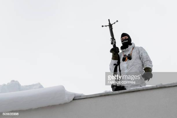 A member of the Swiss special police surveys the area from a rooftop at the opening of the World Economic Forum annual meeting in Davos on January 19...