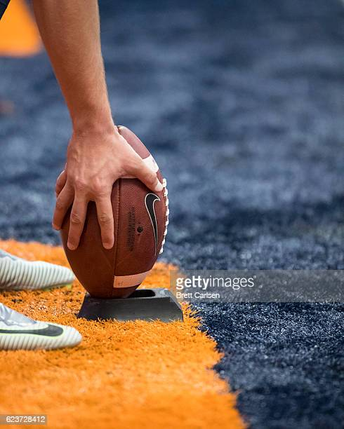A member of the Syracuse Orange places a Nike football on a tee before the game against the North Carolina State Wolfpack on November 12 2016 at The...