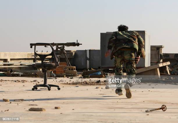 TOPSHOT A member of the Syria government forces guards a position as they battle opposition fighters in the rebelheld town of Harasta in the Eastern...