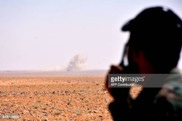 A member of the Syria government forces looks at smoke rising on the horizon from look out point in AlShula on the southwestern outskirts of Deir...