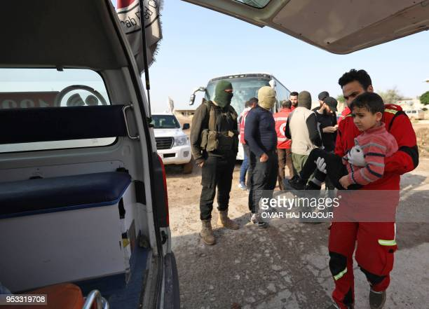 A member of the Syrian Arab Red Crescent carries a wounded child as civilians from the besieged Shiite areas of Fuaa and Kafraya in rebelheld...