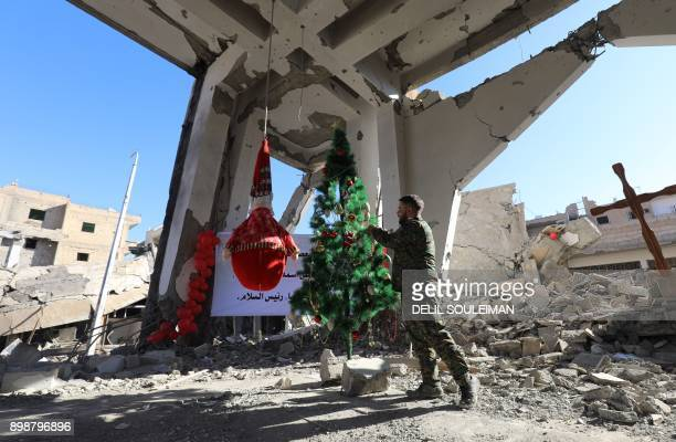 TOPSHOT A member of the Syrian ArabKurdish arranges a tree ahead of a Christmas celebration at the heavilydamaged Armenian Catholic Church of the...
