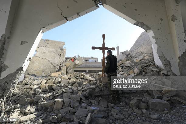 TOPSHOT A member of the Syrian ArabKurdish forces places a cross in the rubble ahead of a Christmas celebration at the heavilydamaged Armenian...