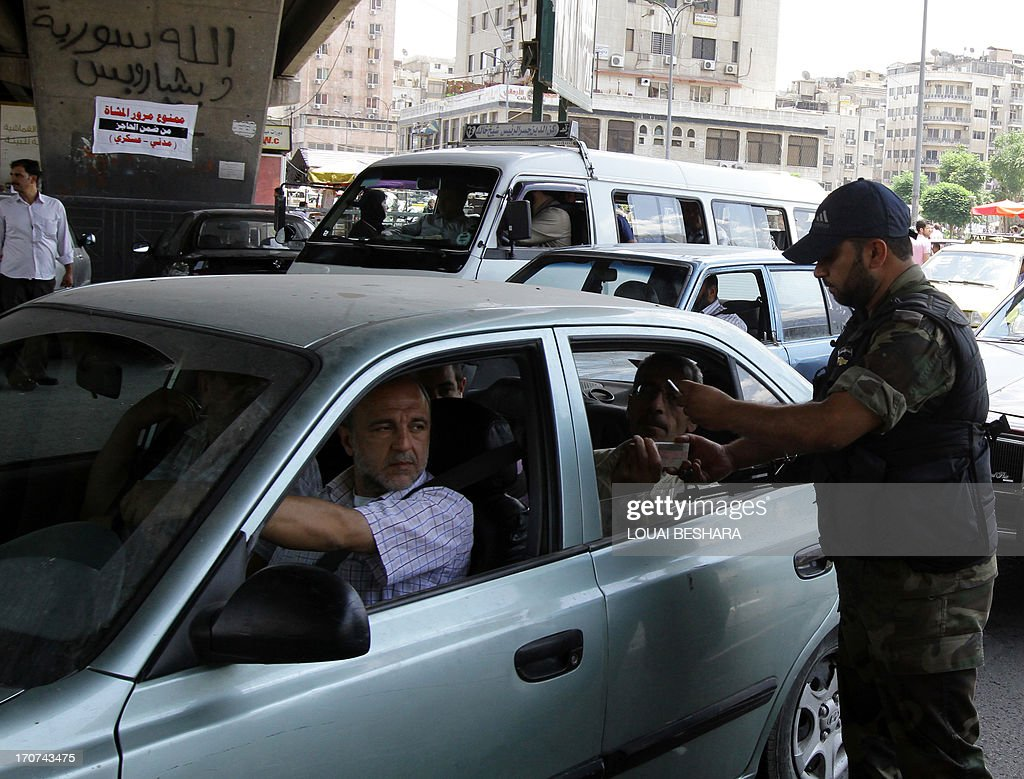 A member of the Syrian army checks the identification card of the passengers at a checkpoint in Damascus on June 17, 2013. Russia said it would not permit a no-fly zone to be implemented over Syria, following reports that plans for such a measure were being drawn up by the United States.