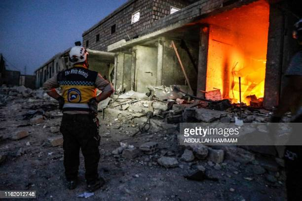 TOPSHOT A member of the Syrian Civil Defence also known as the White Helmets stands outside a burning shop following a reported air strike in Kfar...