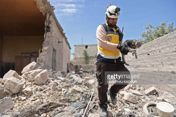 TOPSHOT A member of the Syrian Civil Defence caries a cat amidst rubble from a building damaged during reported shelling by government and allied...
