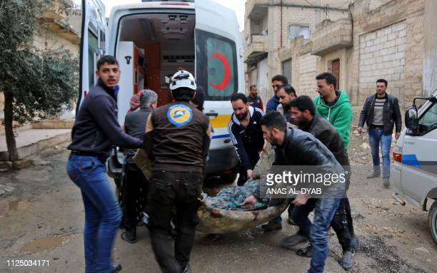 A member of the Syrian Civil Defence carries a wounded woman following a strike in the town of Khan Shaykhun in the southern countryside of the...
