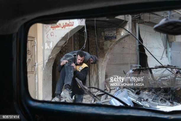 TOPSHOT A member of the Syrian Civil Defence known as the White Helmets carries a wounded man during reported regime shelling on the rebelheld town...