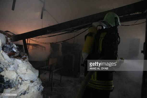 A member of the Syrian Civil Defence puts out a fire at the site of reported air strikes in the town of Khan Sheikhun in the southern countryside of...