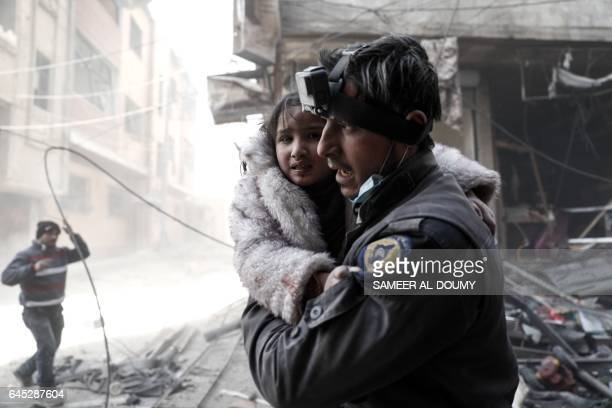 TOPSHOT A member of the Syrian Civil Defence volunteers also known as the White Helmets carries a wounded girl amid the rubble following reported...