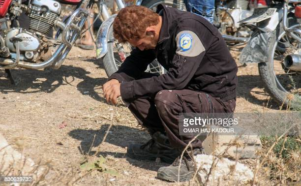 A member of the Syrian civil defence volunteers also known as the White Helmets mourns as colleagues bury his fellow comrades during a funeral in...