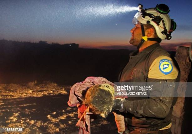 Member of the Syrian Civil Defense carries a young victim following a reported Russian airstrike on the town of Maaret al-Numan in Syria's...