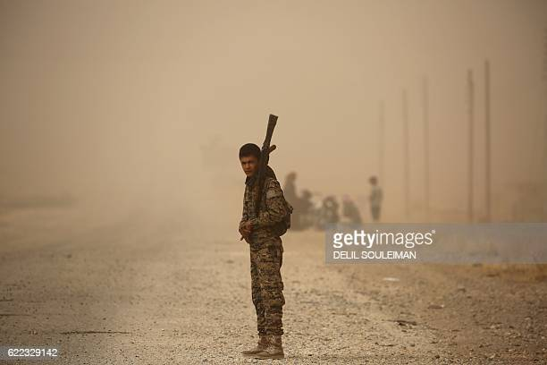 Member of the Syrian Democratic Forces , a US-backed Kurdish-Arab alliance, stands at attention during a sandstorm at a temporary refugee camp in the...