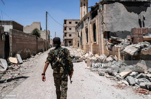 TOPSHOT A member of the Syrian Democratic Forces an alliance of Kurdish and Arab fighters walks on a damaged street in western Raqa on July 12 during...