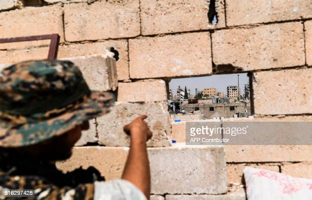 TOPSHOT A member of the Syrian Democratic Forces an alliance of Kurdish and Arab fighters points at sniper positions of Islamic State fighters in...