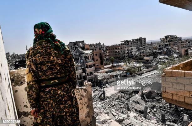 TOPSHOT A member of the Syrian Democratic Forces backed by US special forces monitors the area on the western frontline in Raqa on October 8 2017 The...