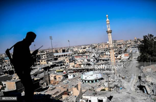 TOPSHOT A member of the Syrian Democratic Forces backed by US special forces talks on the radio near Raqa's stadium as they clear the last positions...