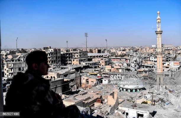 A member of the Syrian Democratic Forces backed by US special forces monitors the a from a building near Raqa's stadium as they clear the last...