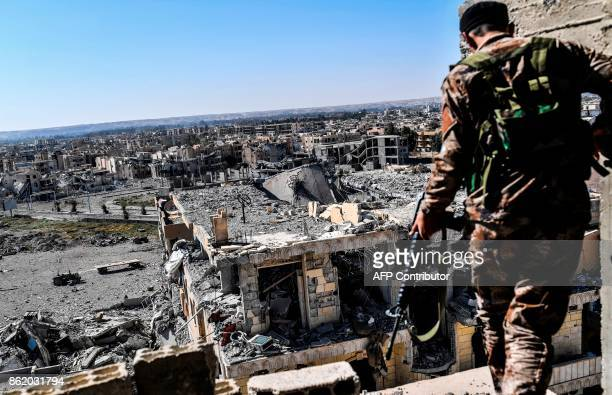 A member of the Syrian Democratic Forces backed by US special forces walks on a building near Raqa's stadium as they clear the last positions on the...