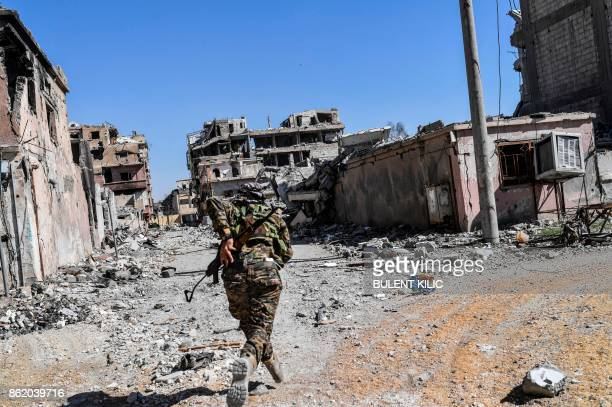 TOPSHOT A member of the Syrian Democratic Forces backed by US special forces runs as he tries to take a cover near Raqa's stadium as they clear the...