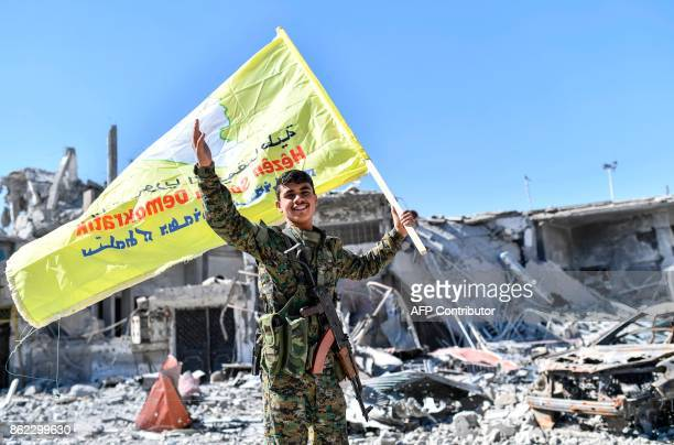 A member of the Syrian Democratic Forces backed by US special forces holds up their flag at the iconic AlNaim square in Raqa on October 17 2017...