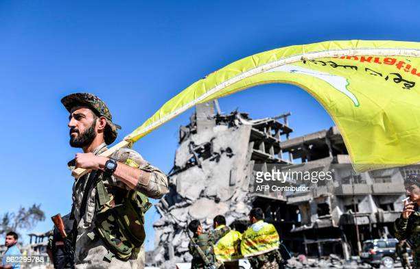 TOPSHOT A member of the Syrian Democratic Forces backed by US special forces holds up their flag at the iconic AlNaim square in Raqa on October 17...