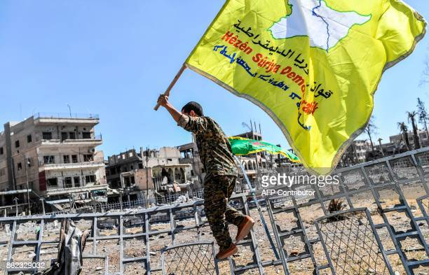 A member of the Syrian Democratic Forces backed by US special forces holds up his group's flag at the iconic AlNaim square in Raqa on October 17 2017...