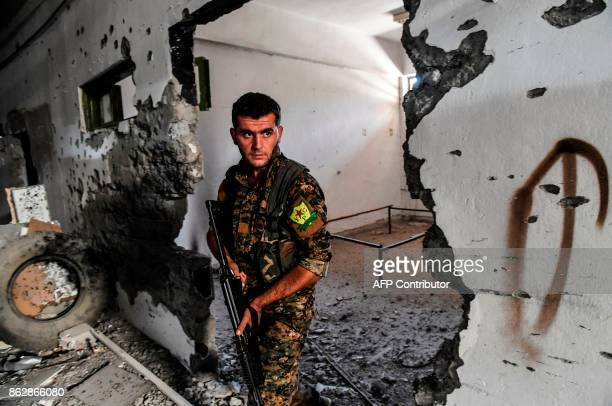 A member of the Syrian Democratic Forces inspects the municipal stadium in Raqa on October 18 after the USbacked forces retook the city from Islamic...