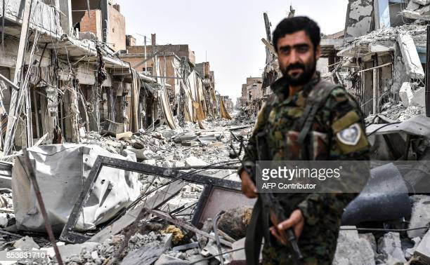 A member of the Syrian Democratic Forces looks at the destruction in a street in the old city centre on the eastern frontline of Raqa on September 25...