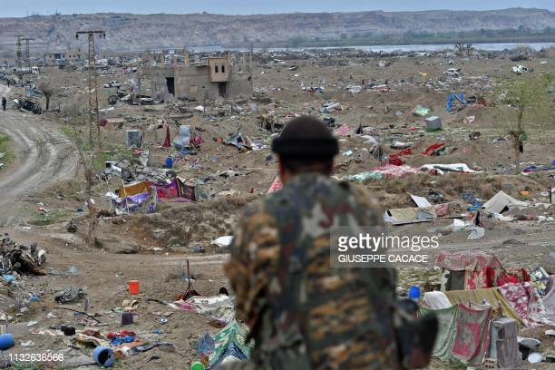 Member of the Syrian Democratic Forces looks on while on watch duty in the village of Baghouz in Syria's eastern Deir Ezzor province near the Iraqi...