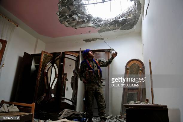 TOPSHOT A member of the Syrian Democratic Forces made up of an alliance of Kurdish and Arab fighters looks at the damage in a neighbourhood on the...
