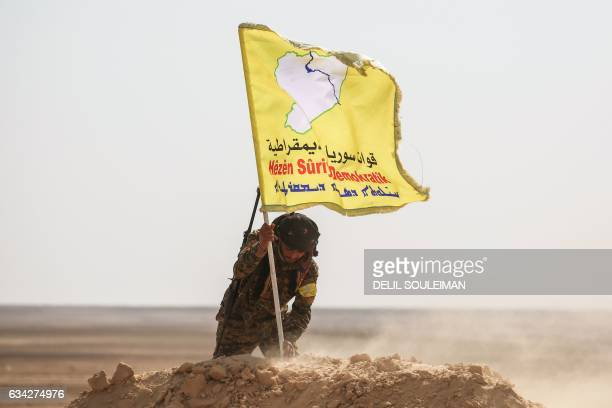 A member of the Syrian Democratic Forces made up of USbacked Kurdish and Arab fighters raises a flag of the SDF near the village of Bir Fawaz 20 km...
