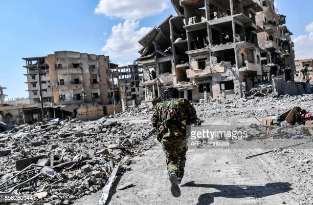 TOPSHOT A member of the Syrian Democratic Forces runs to take cover from sniper shots near the central hospital of Raqa on October 1 2017 Syrian...