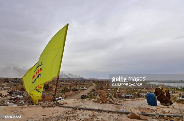 A member of the Syrian Democratic Forces sits next to a barrel atop a roof with the SDF's unfurled flag at a position in the village of Baghouz in...